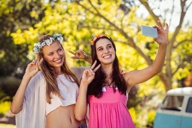 友達が携帯電話で自分撮りをクリックする