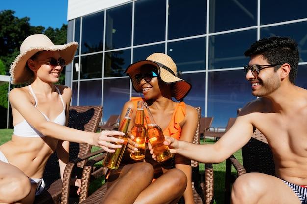 友達はプールの近くでビールとボトルをチリンと鳴らします。夏休み、屋外のプールサイドでのホリデーパーティーを楽しんでいる幸せな人々。 1人の男性と2人の女性が日光浴をしています