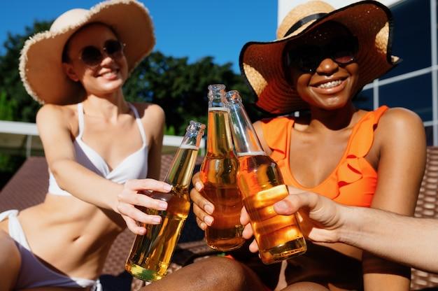 친구들은 수영장 근처에서 맥주와 함께 병을 찰칵. 여름 방학에 즐거운 시간을 보내는 행복한 사람들, 야외 수영장에서 일광욕을 하는 휴가 파티