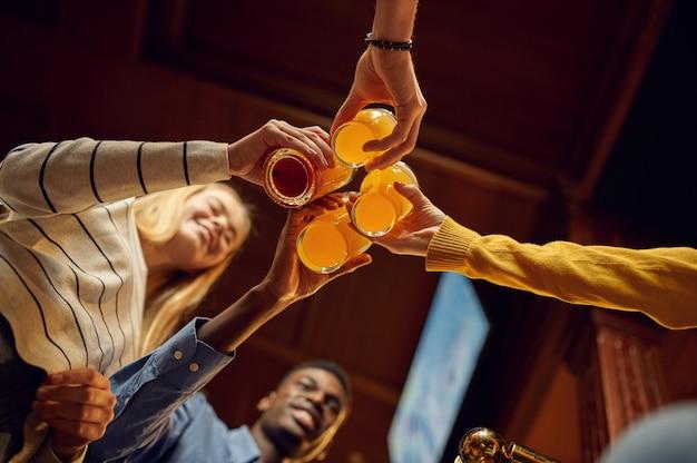 Друзья чокаются с пивом за стойкой в баре. группа людей отдыхает в пабе, ночной образ жизни, дружба, празднование события