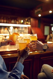 Friends clink glasses with beer at the counter in bar. group of people relax in pub, night lifestyle, friendship, event celebration
