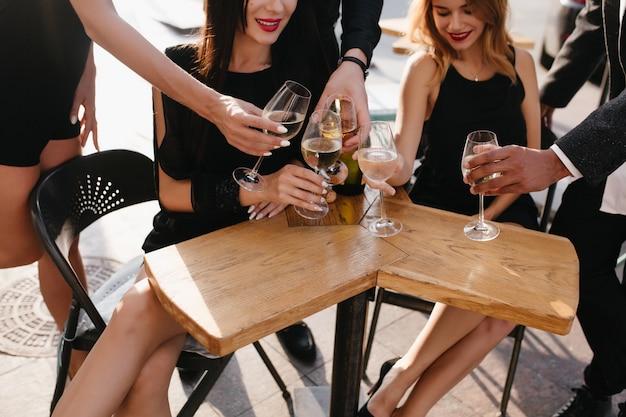Amici tintinnanti e bevendo champagne su una terrazza