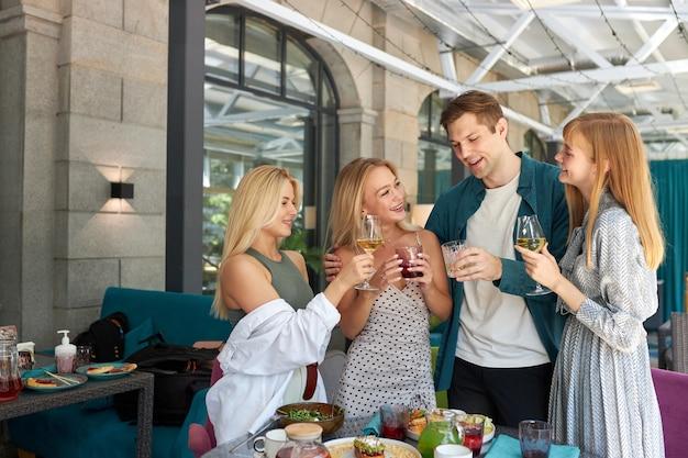 レストランの夕食のテーブルの上でグラスをチリンと鳴らす友人