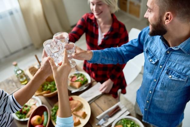 Friends clinking glasses at thanksgiving dinner