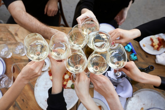 Друзья чокаются с белым вином во время вечеринки на открытом воздухе