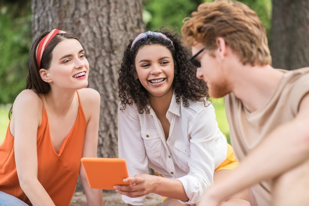 Friends, communication. guy in sunglasses and two smiling girlfriends with tablet friendly chatting at picnic in park