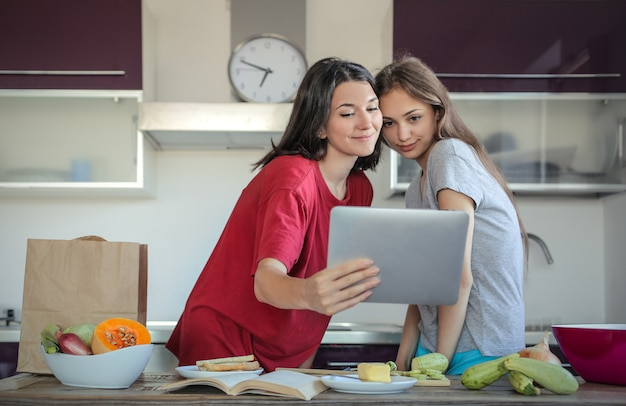 Friends cooking together and using a tablet