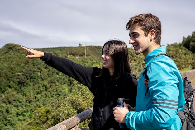 Friends couple hiking up the mountain exploring forest nature