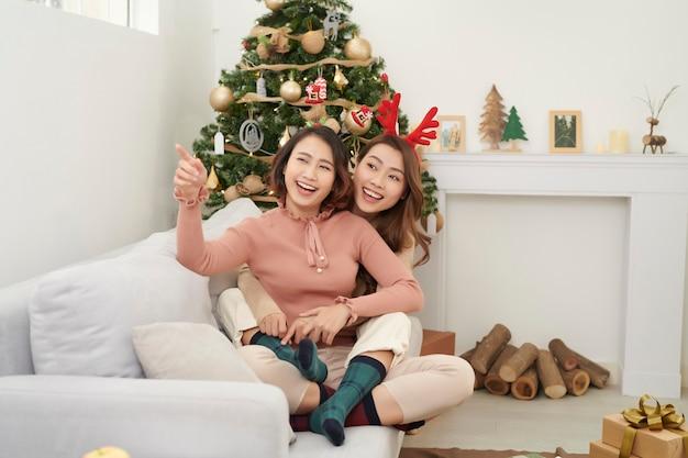 自宅のリビングルームのソファに座ってクリスマスの日に抱きしめる友人
