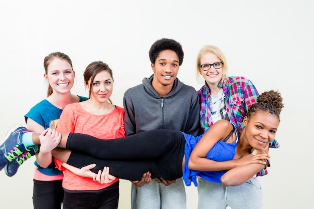 Friends in dance class carrying woman on hands