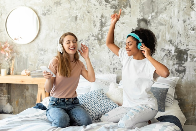 Friends dancing on bed at home