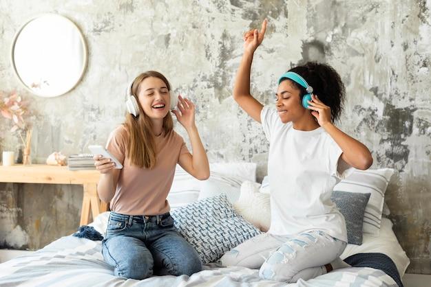 Друзья танцуют на кровати у себя дома