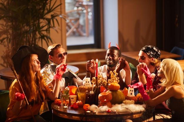 Друзья, обедающие на вечеринке в честь хэллоуина