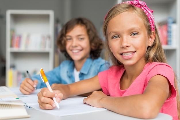 Друзья вместе делают домашнее задание в библиотеке