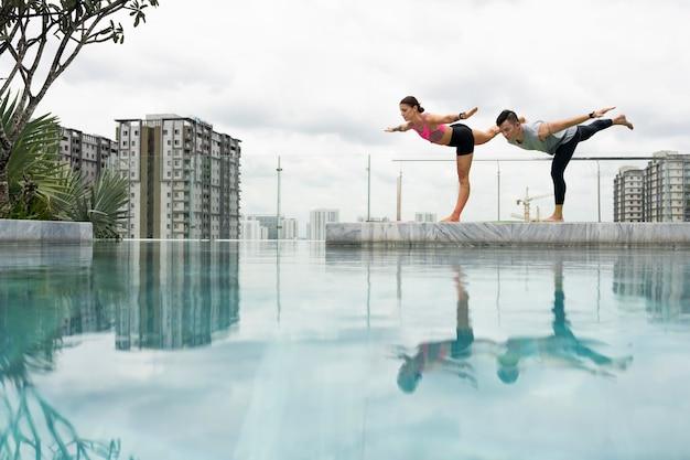 Amici che fanno yoga insieme in piscina