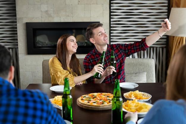 Друзья пьют пиво, едят пиццу, разговаривают, смеются и снимают селфи на камеру смартфона