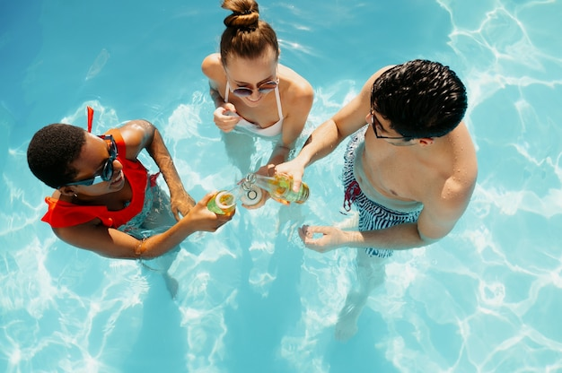 Friends drink beverages in the pool, top view