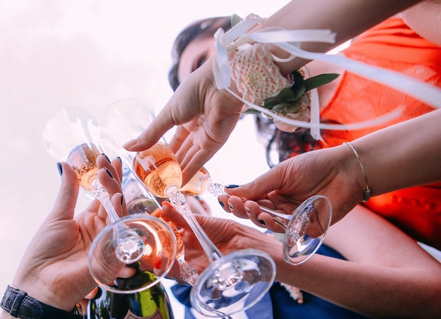 Friends drink champagne raise glasses outside sky