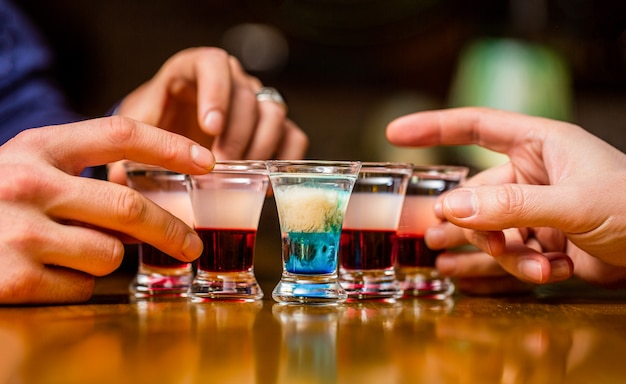 Friends drink shot or liqueur. five glasses of alcohol.tequila shots, vodka, whisky, rum. cocktail at the nightclub. group friends tequila shot glasses in bar. male hands glasses of shot or liqueur.