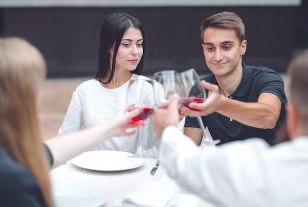 Друзья пьют вино в ресторане.