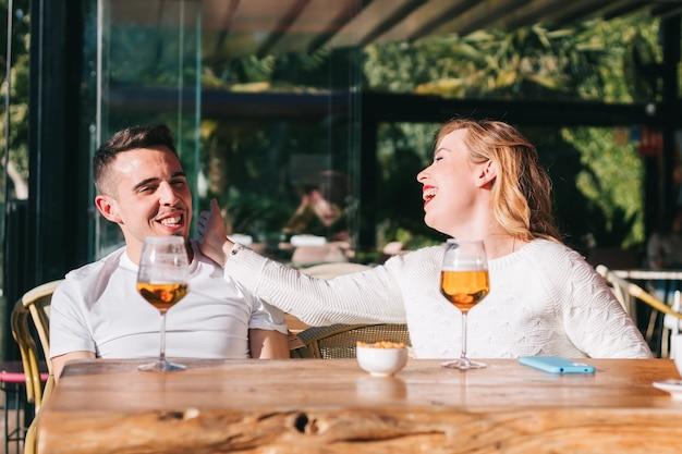 バーやレストランで友達と会いながらビールを飲む友達。