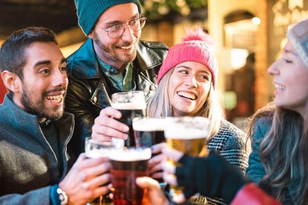 ビールを飲み、冬時間に屋外のビール醸造所バーで楽しんでいる友人