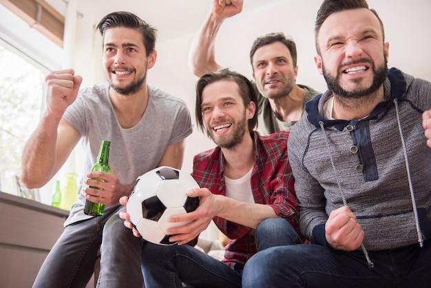 ビールを飲み、サッカーの試合を見ている友達