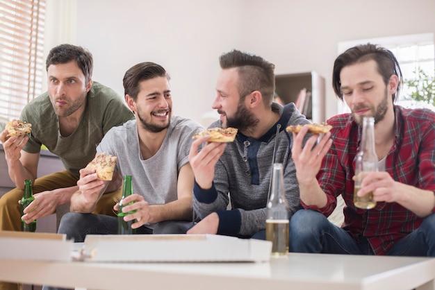 Amici che bevono birra e mangiano pizza