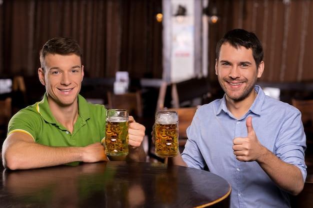 맥주를 마시는 친구. 맥주와 함께 머그잔을 들고 카메라를 보며 웃고 있는 두 젊은이