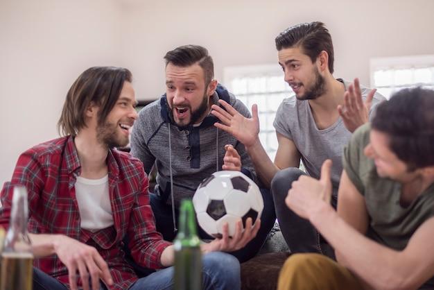 Amici che bevono birra e guardano la partita di calcio