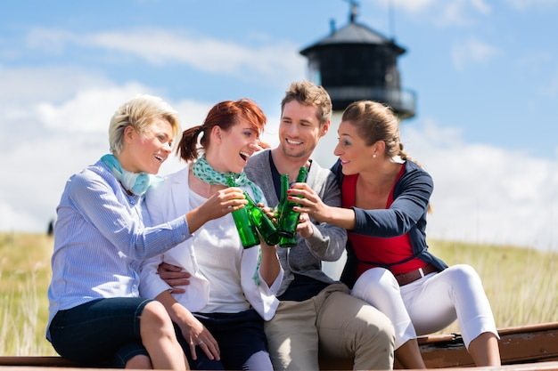 Друзья пьют пиво в бутылках на пляже