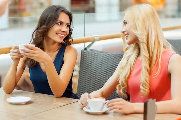 Друзья пьют кофе. две красивые молодые женщины, наслаждаясь чашкой кофе в кафе