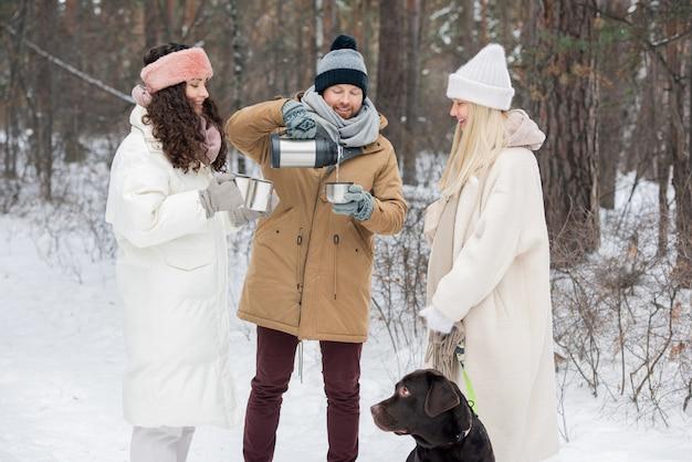 Друзья пьют горячий чай на открытом воздухе