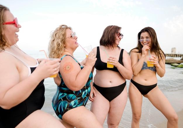 Amici che bevono succo alla vista lunga della spiaggia