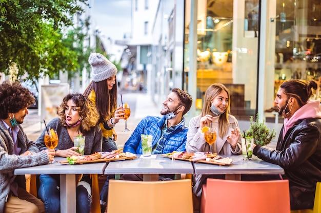 フェイスマスク付きのカクテルバーでスプリッツとモヒートを飲む友人-レストランで飲み物を乾杯して一緒に楽しんでいる幸せな人々との新しい通常の友情の概念