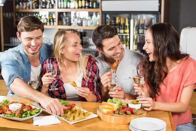 Друзья пьют белое вино и едят