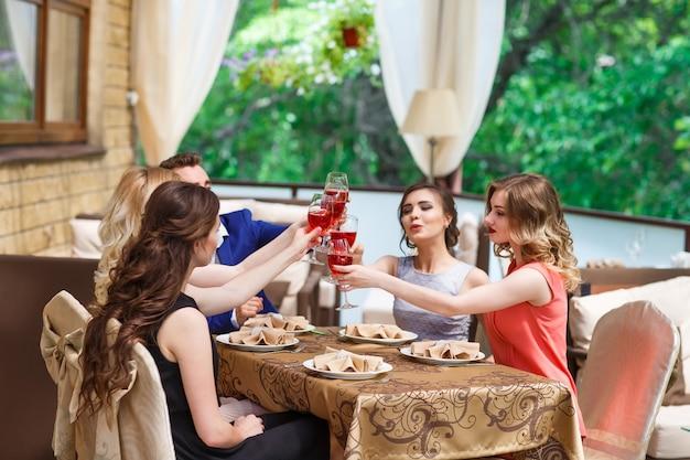 Friends drinking wine on the summer terrace.
