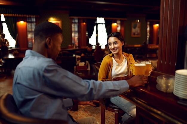Друзья пьют пиво и разговаривают за стойкой в баре. группа людей отдыхает в пабе, ночной образ жизни, дружба, празднование события