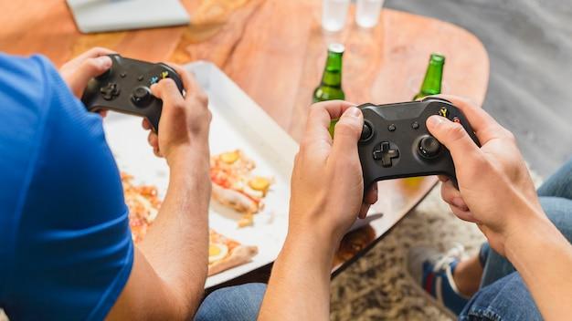 Друзья едят пиццу и играют на консоли