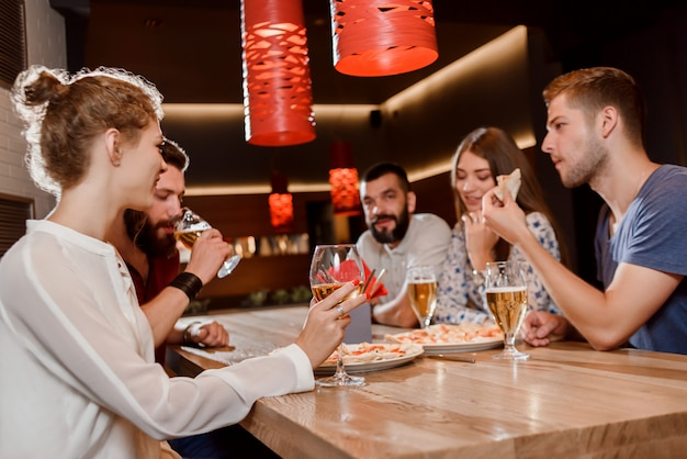 Friends eating pizza and drinking beer in pizzeria.