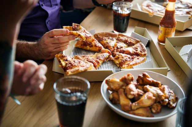 Друзья едят пиццу вместе дома