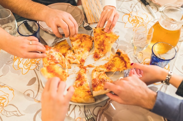 Friends eating pizza together, hands grabbing pieces