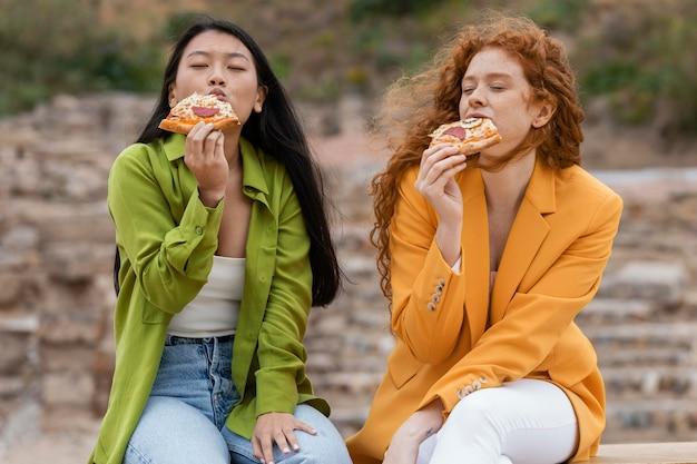 屋外で屋台の食べ物を食べる友達