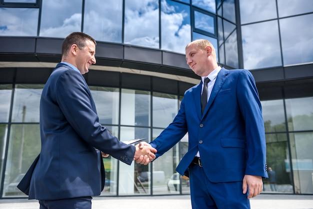 Friends in elegant business suits handshaking outdoors