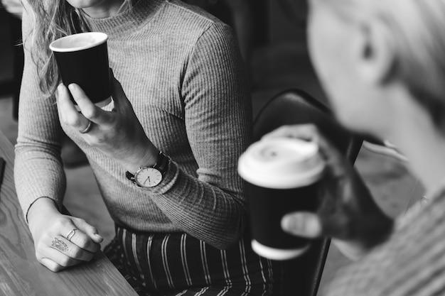 Друзья наслаждаются горячим кофе вместе Бесплатные Фотографии