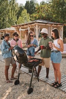 해변 파티를 즐기는 친구들은 구운 핫도그를 만들고 담소를 나누며 맥주를 마시고 있습니다.