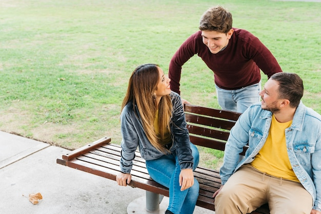 Friends enjoying day in park sitting on bench