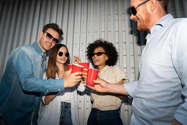 Друзья наслаждаются напитками из пластиковых стаканчиков