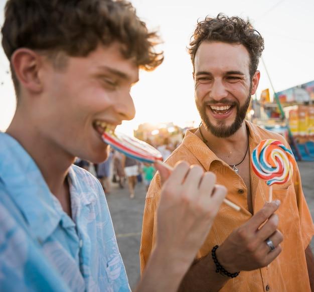 Friends enjoying lollypop at the funfair