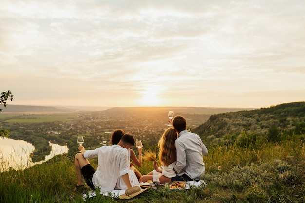 Friends enjoying picnic day and drink white wine together.